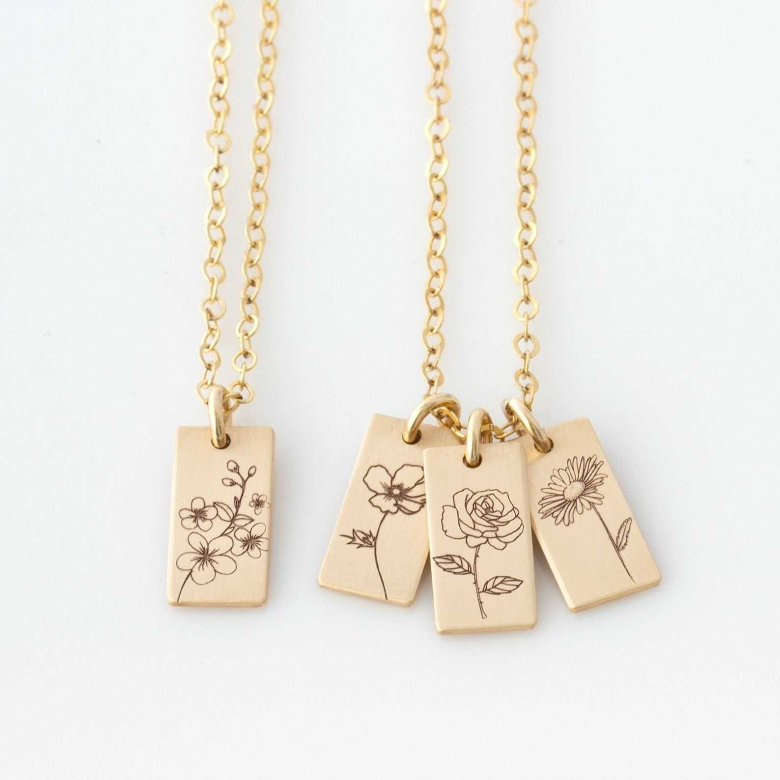 two gold necklaces with rectangular charms on them with flowers on each charm
