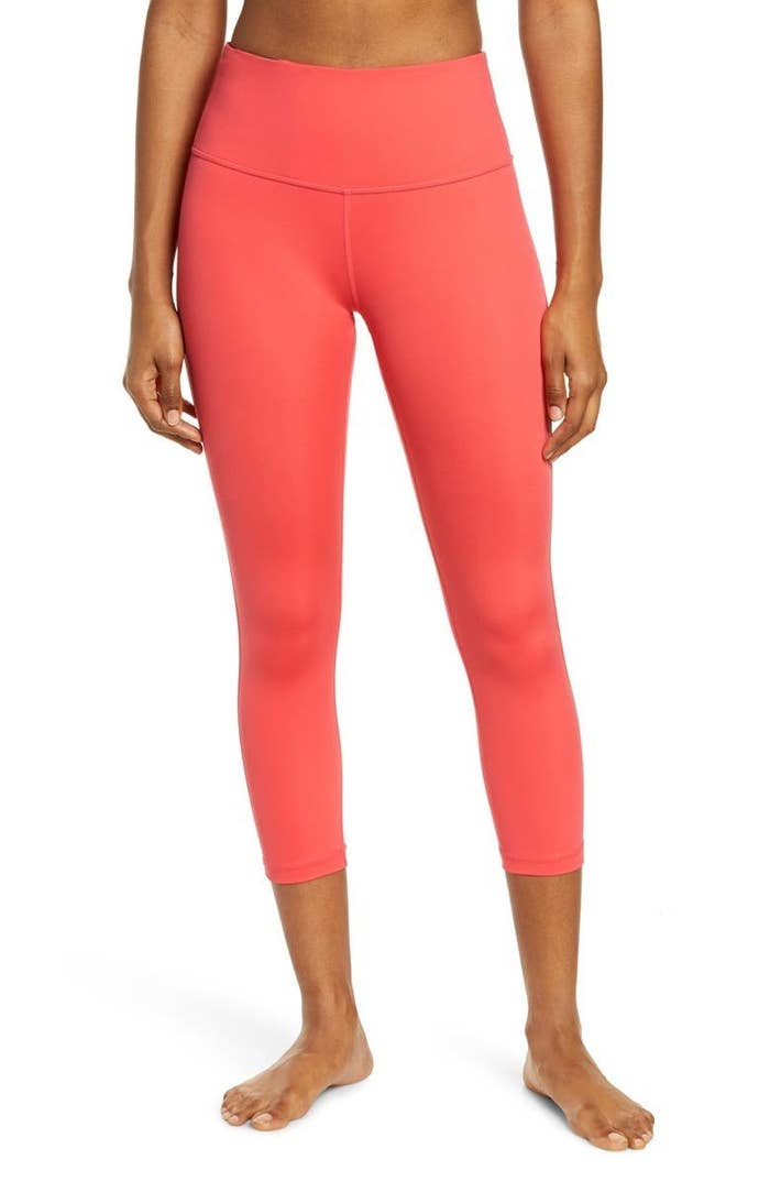 A model wears the leggings in Pink Paradise (coral)