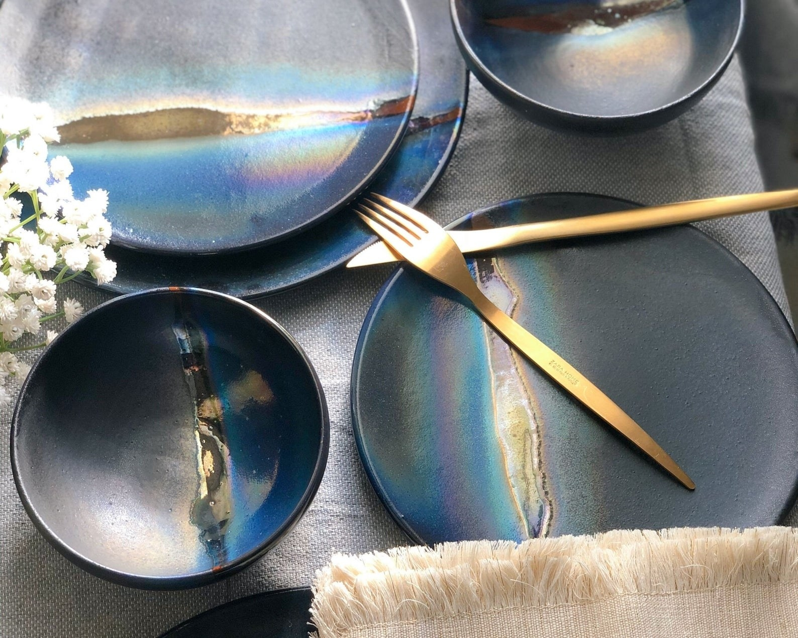 the complete black dinner set with blue and hold metallic luster on a table set with gold utensils