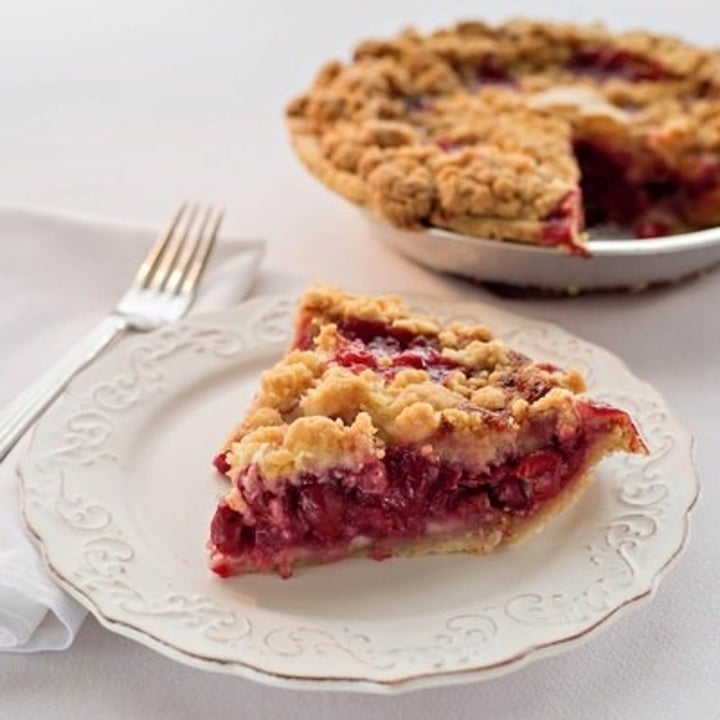A slice of the cherry crumb pie next to the rest of the pie
