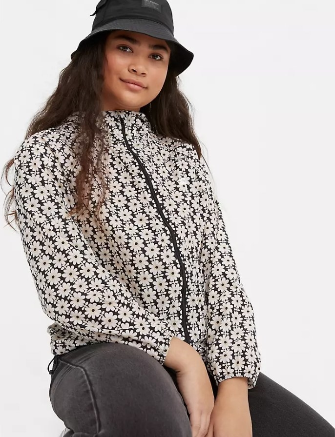 Model wearing windbreaker jacket with white and black flowers