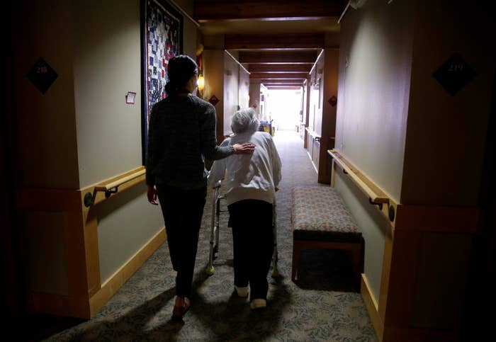 A younger woman and an older woman with a walker go down a hallway