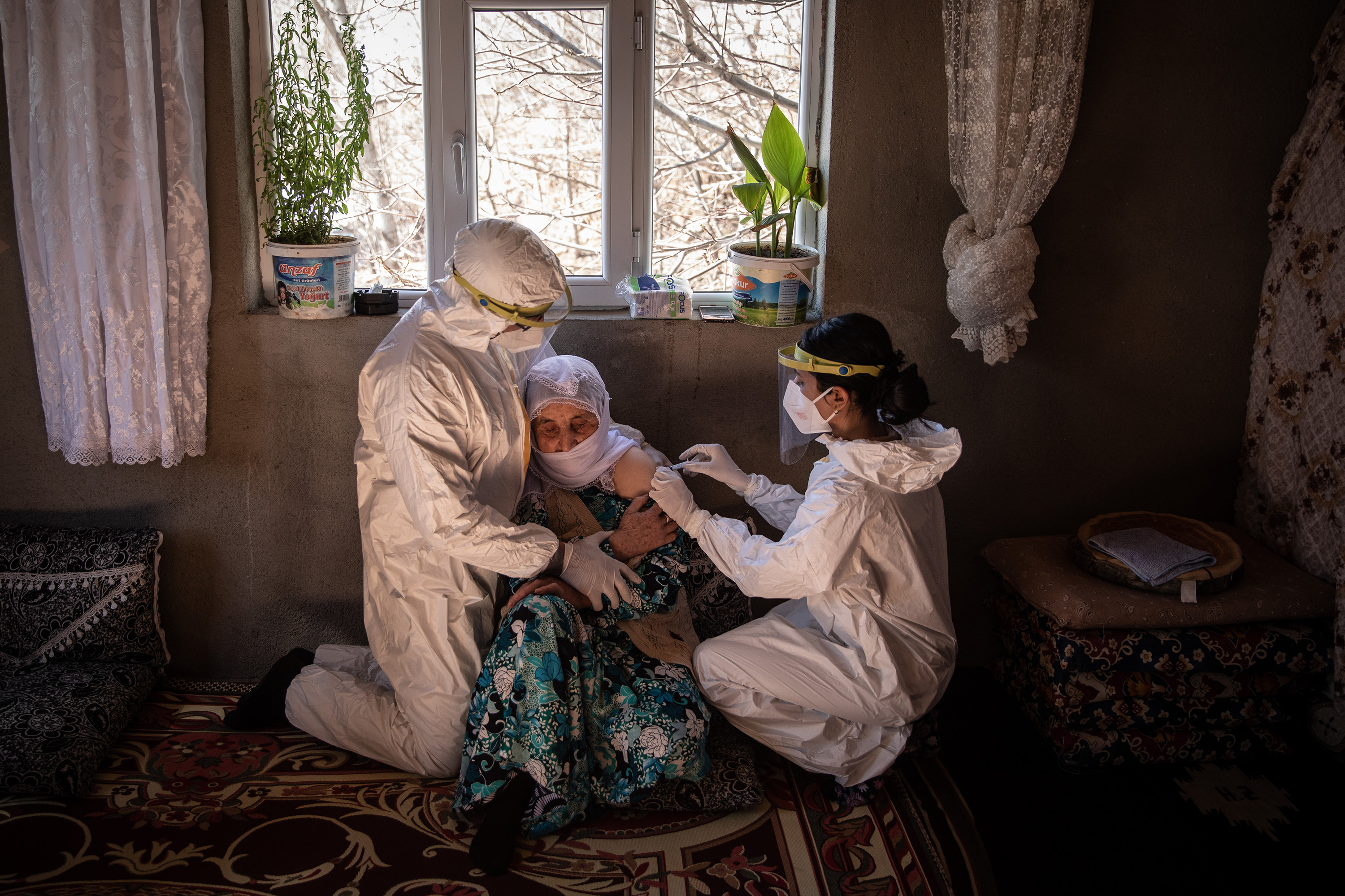 An older Turkish woman sits on the floor of her home as two nurses in haz mat gear administer the vaccine