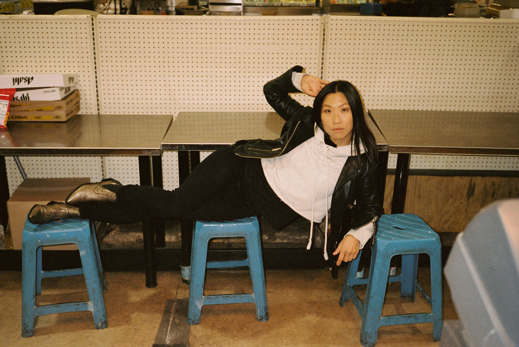 A young woman lies across three stools  and looks at the camera