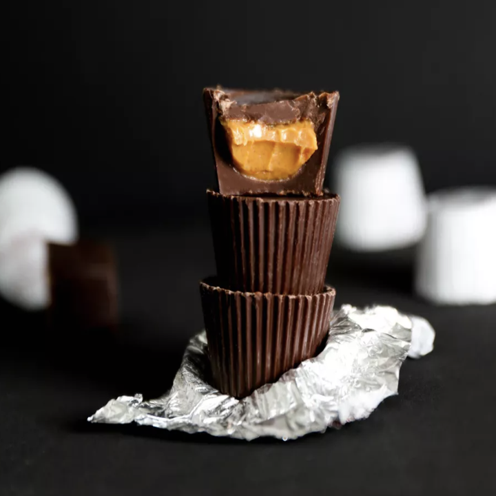 Three dark chocolate peanut butter cups, one broken open so the inside is visible