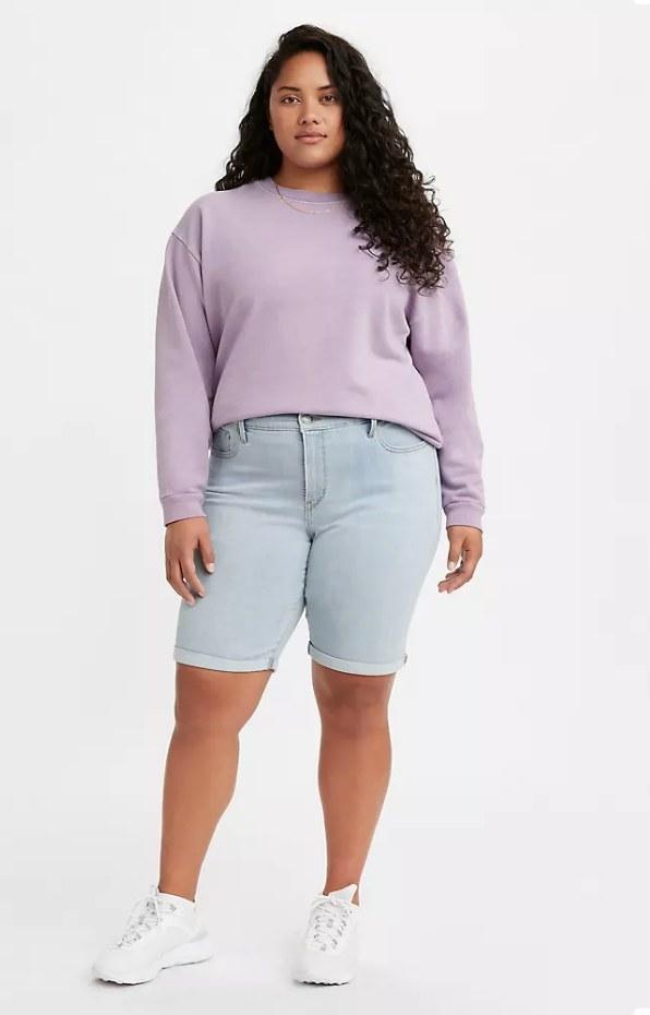 Model wearing light wash bermuda shorts with purple crewneck