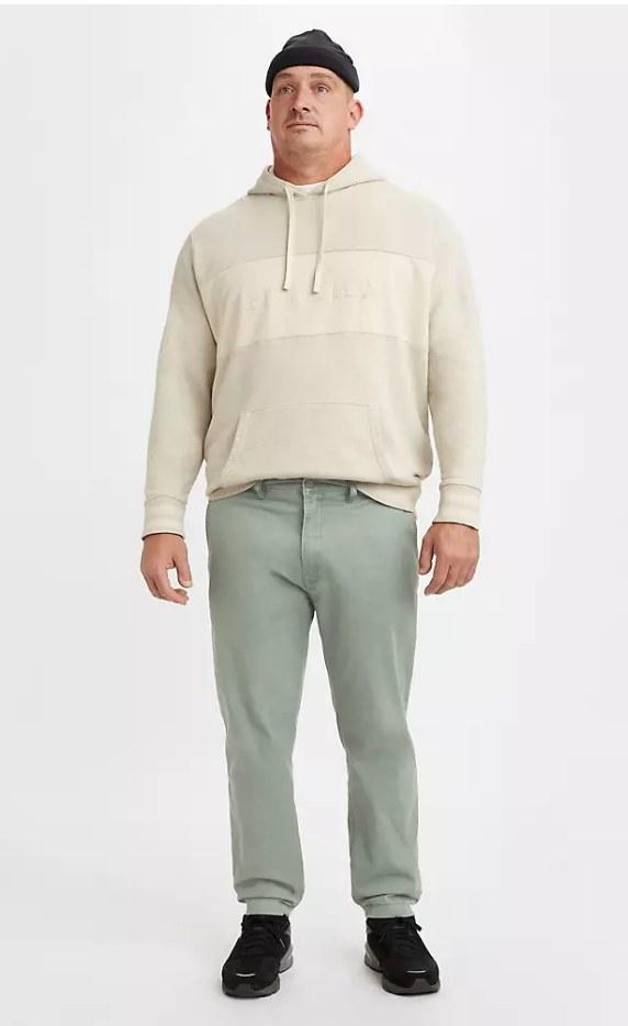Model wearing green chino pants with beige hoodie
