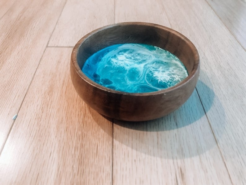 a wooden bowl with resin in the middle to look like ocean waves