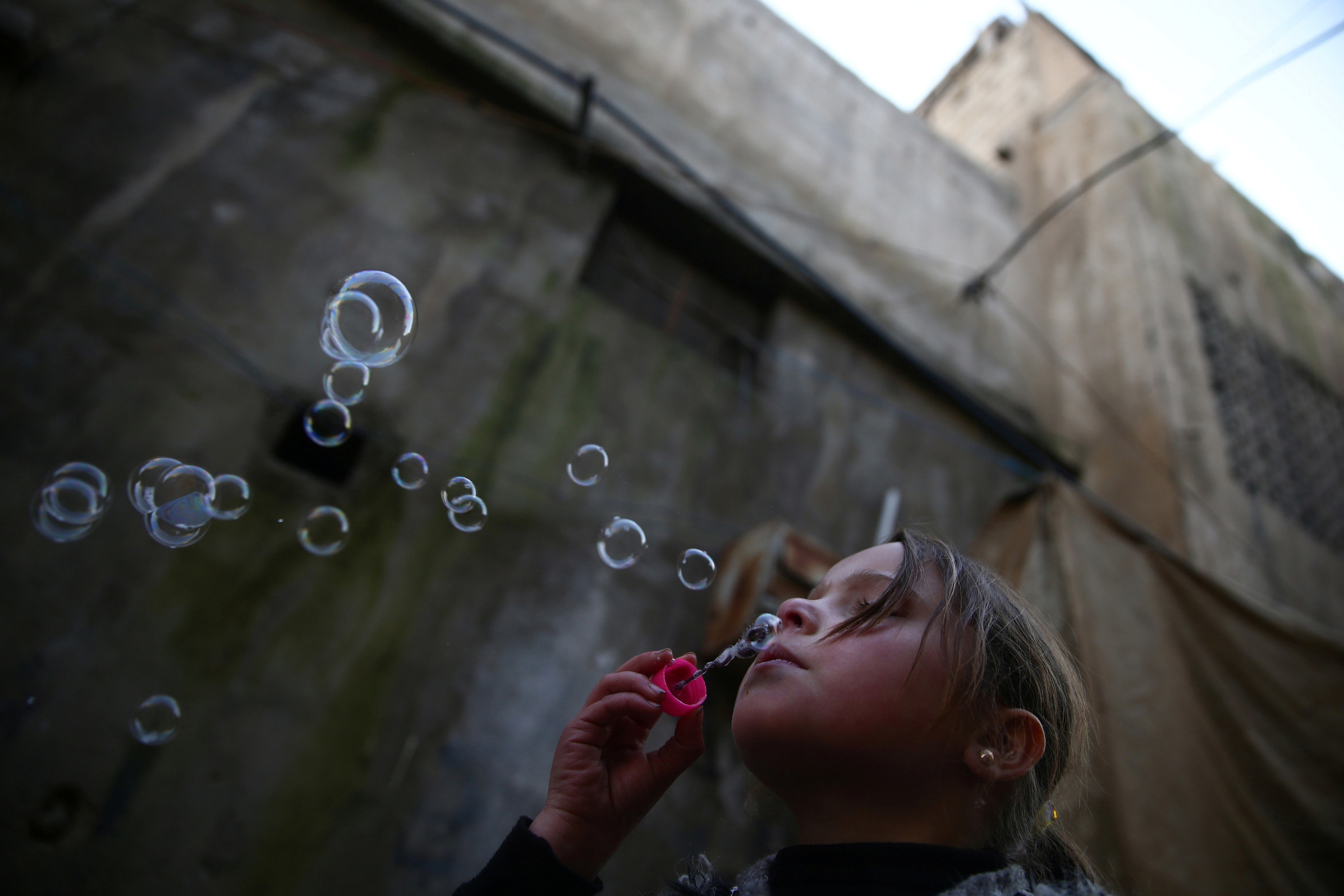 A Syrian girl blows bubbles next to a weathered building