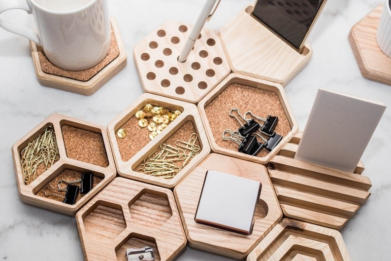 The honeycomb organizers with paperclips, push pins, and other office supplies