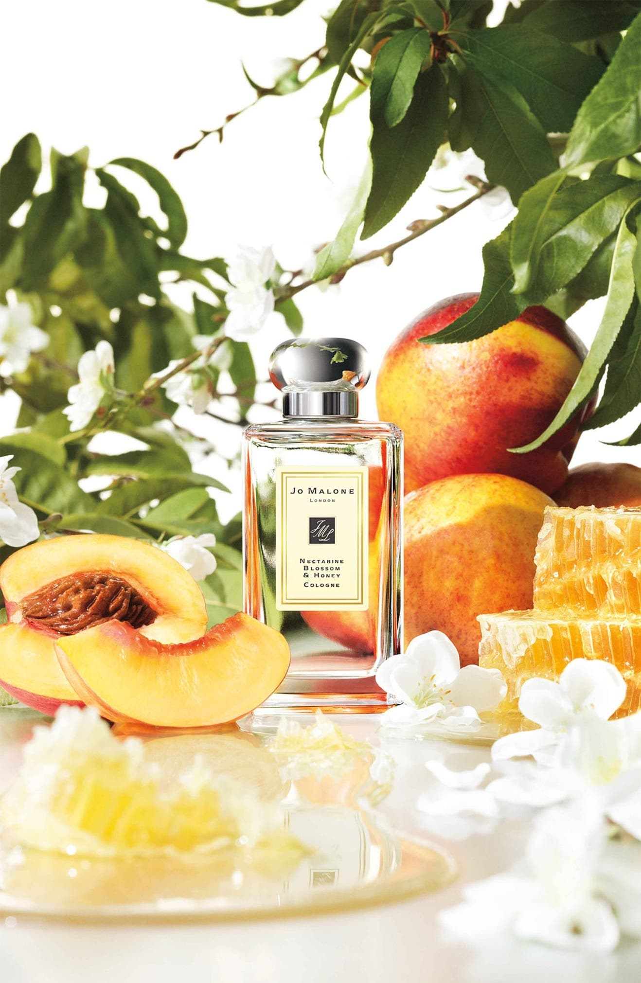 The perfume bottle on a table with nectarines and honeycomb