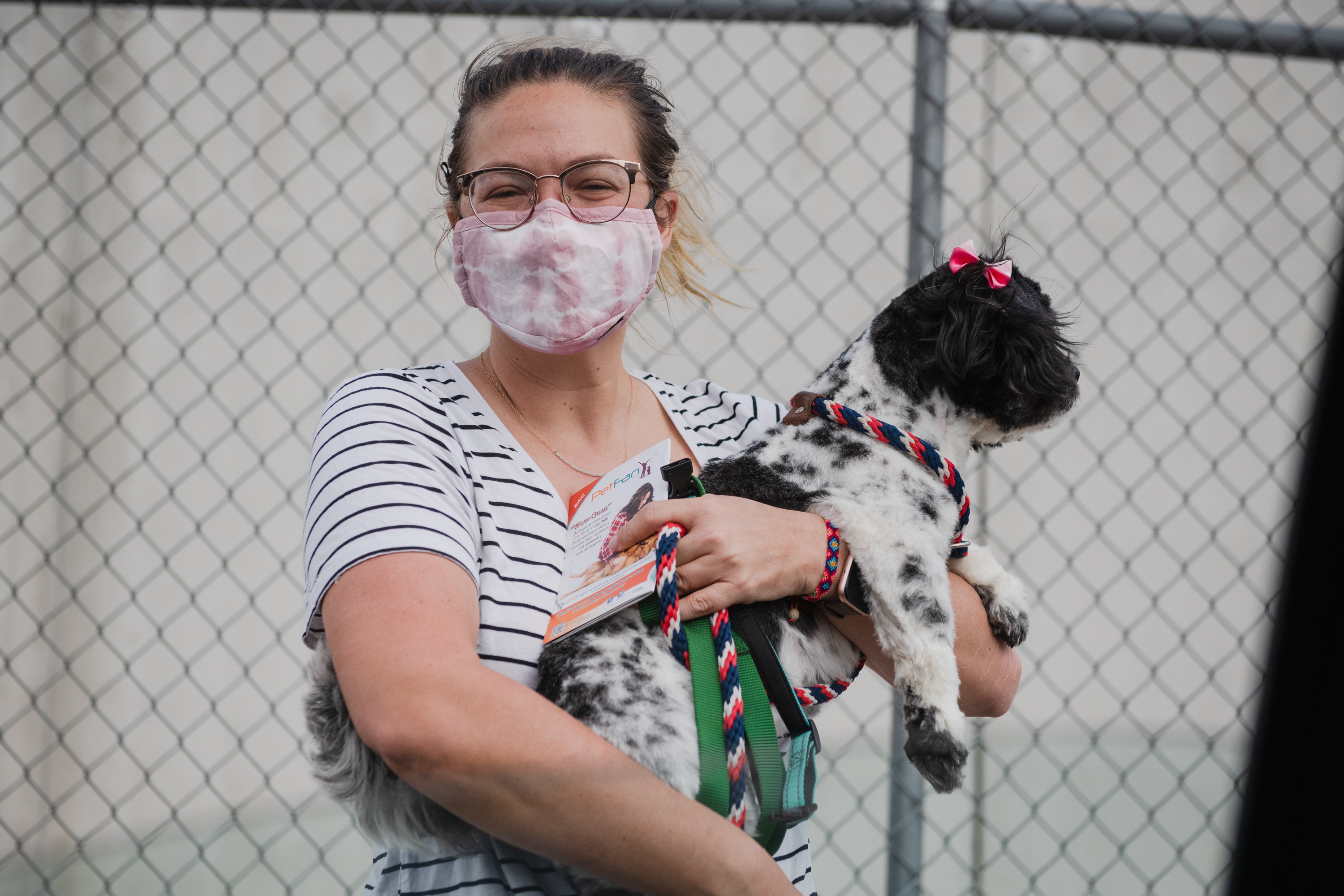 A woman wearing a face masks smiles widely and holds a small dog with a bow above its ear