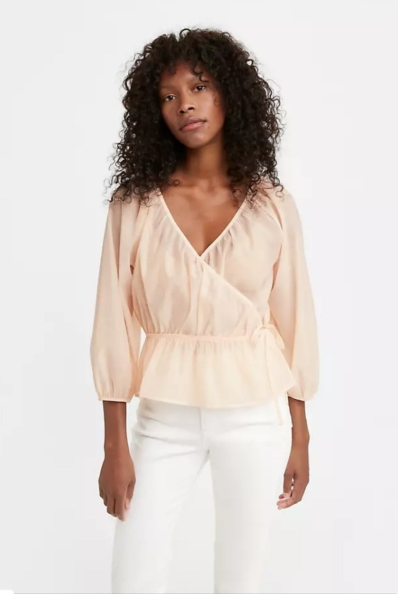 Model wearing puff-sleeve, light pink top with white pants