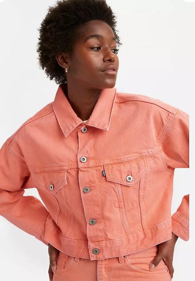 Model wearing cropped salmon colored denim jacket