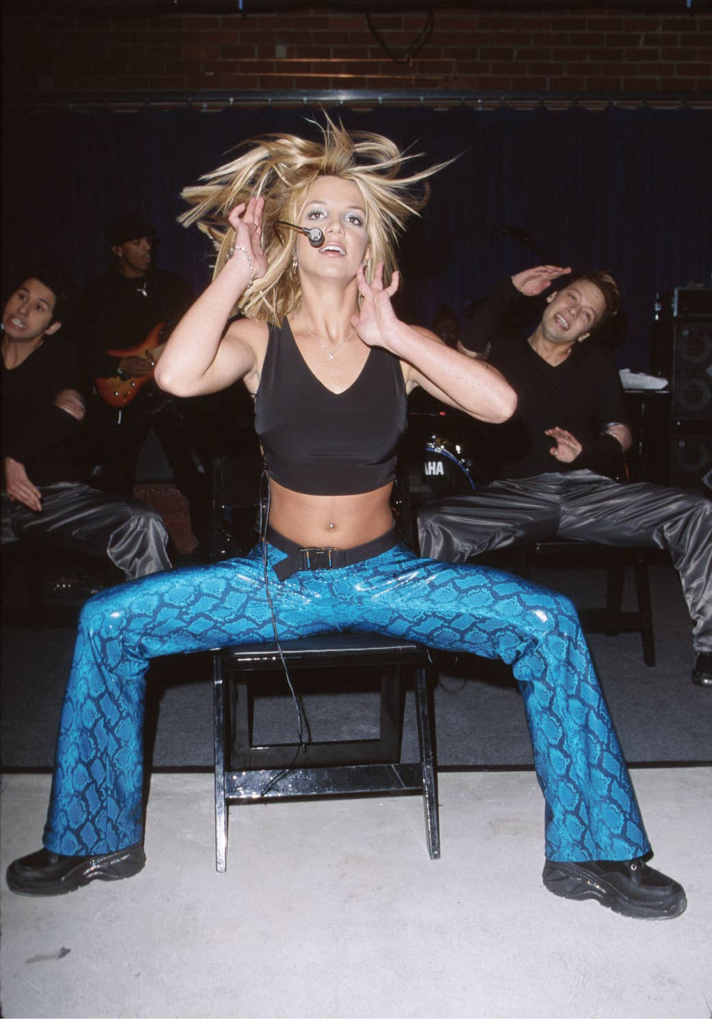 Britney Spears wears a tank top and blue patterned pants as she dances on a chair