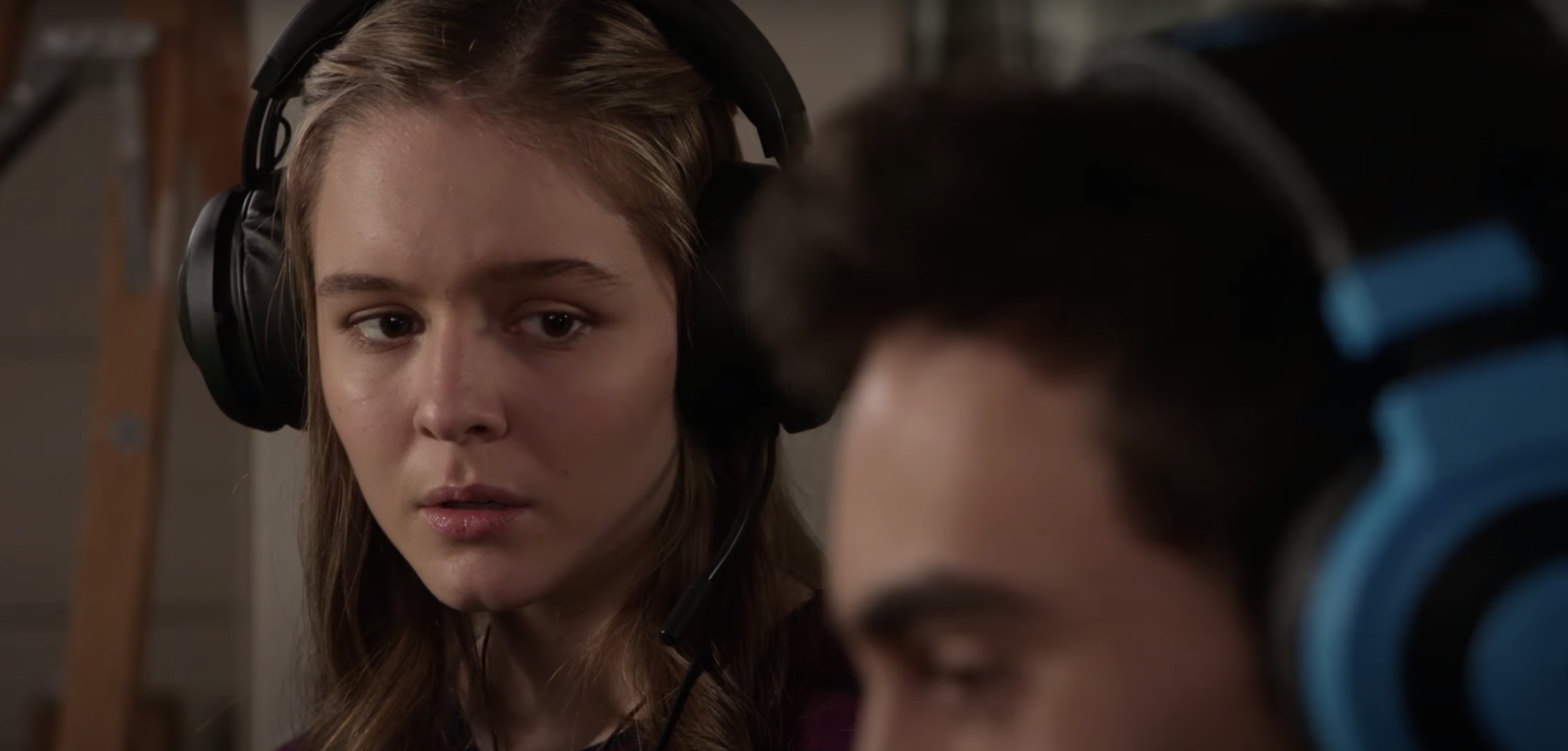 A young woman with a headset on looks upset