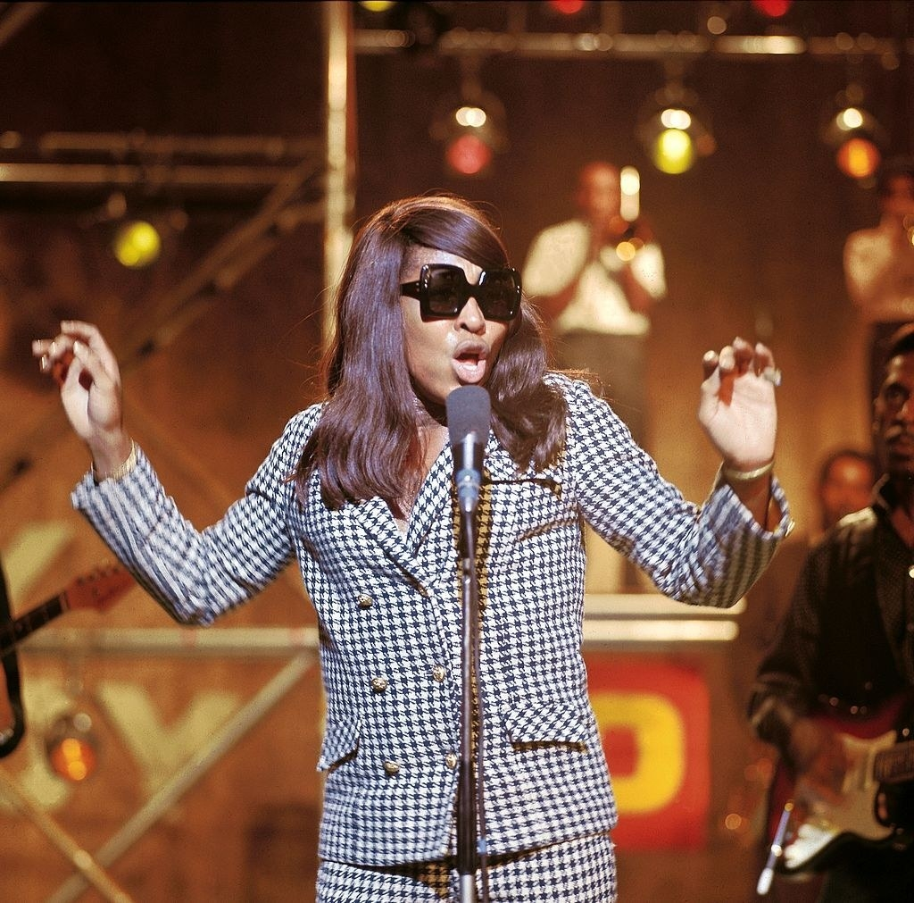 A young Tina Turner wears a hounds tooth suit with sunglasses