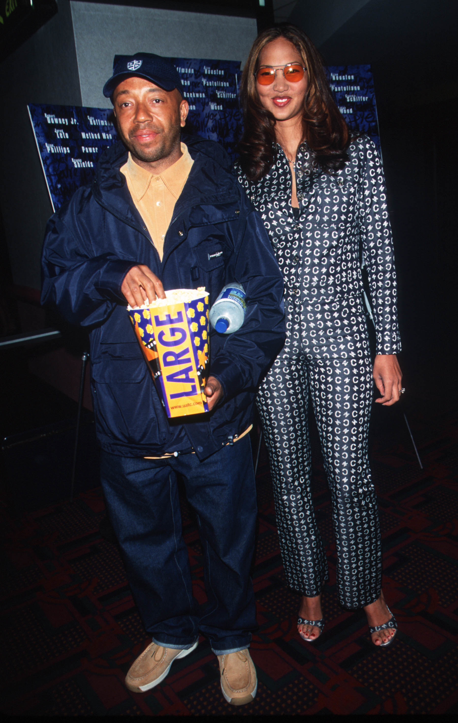 Russell Simmons with popcorn with wife Kimora Lee Simmons in a printed suit