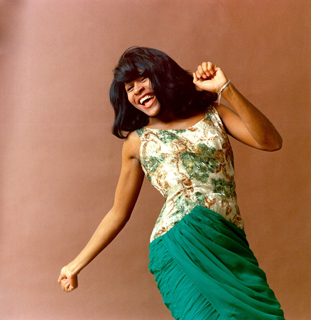 A young Tina Turner dances in a green dress
