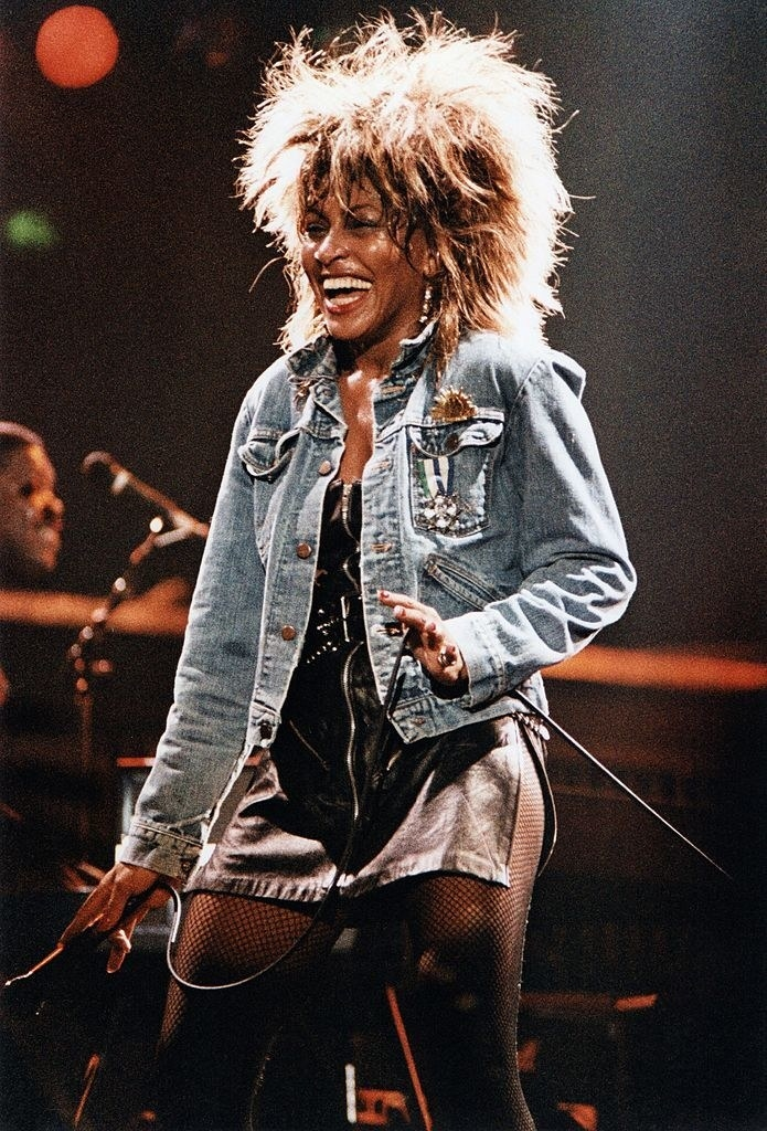 Tina Turner in a jean jacket, a leather miniskirt, and fish net tights