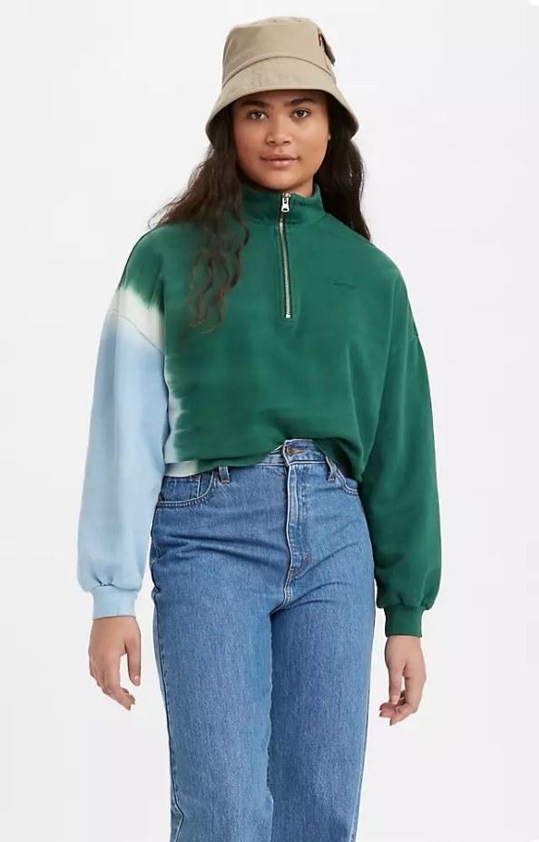 a model in a green and blue tie dye sweatshirt