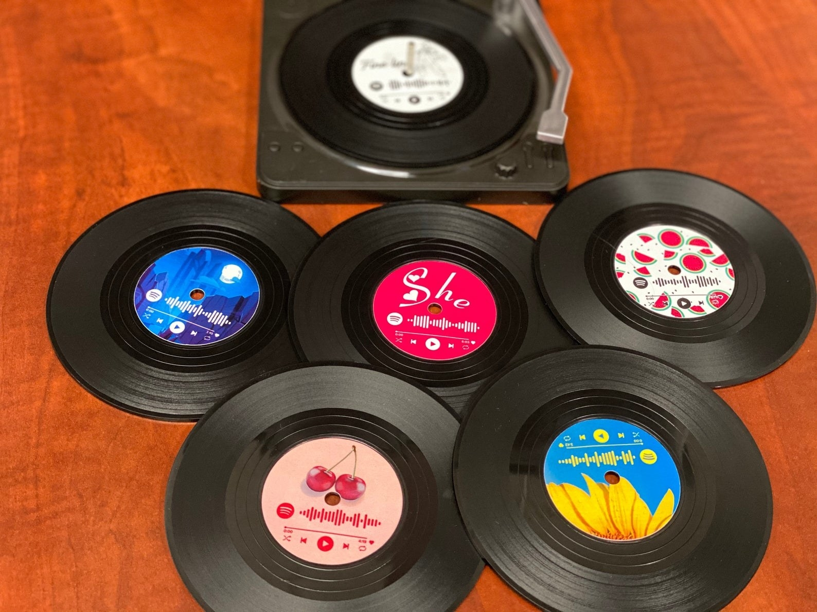 Five coasters that look like vinyl records with themes from Harry Styles songs and spotify codes leading to them