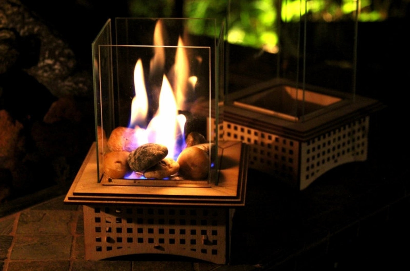 A mini glass encased fireplace burning on a table