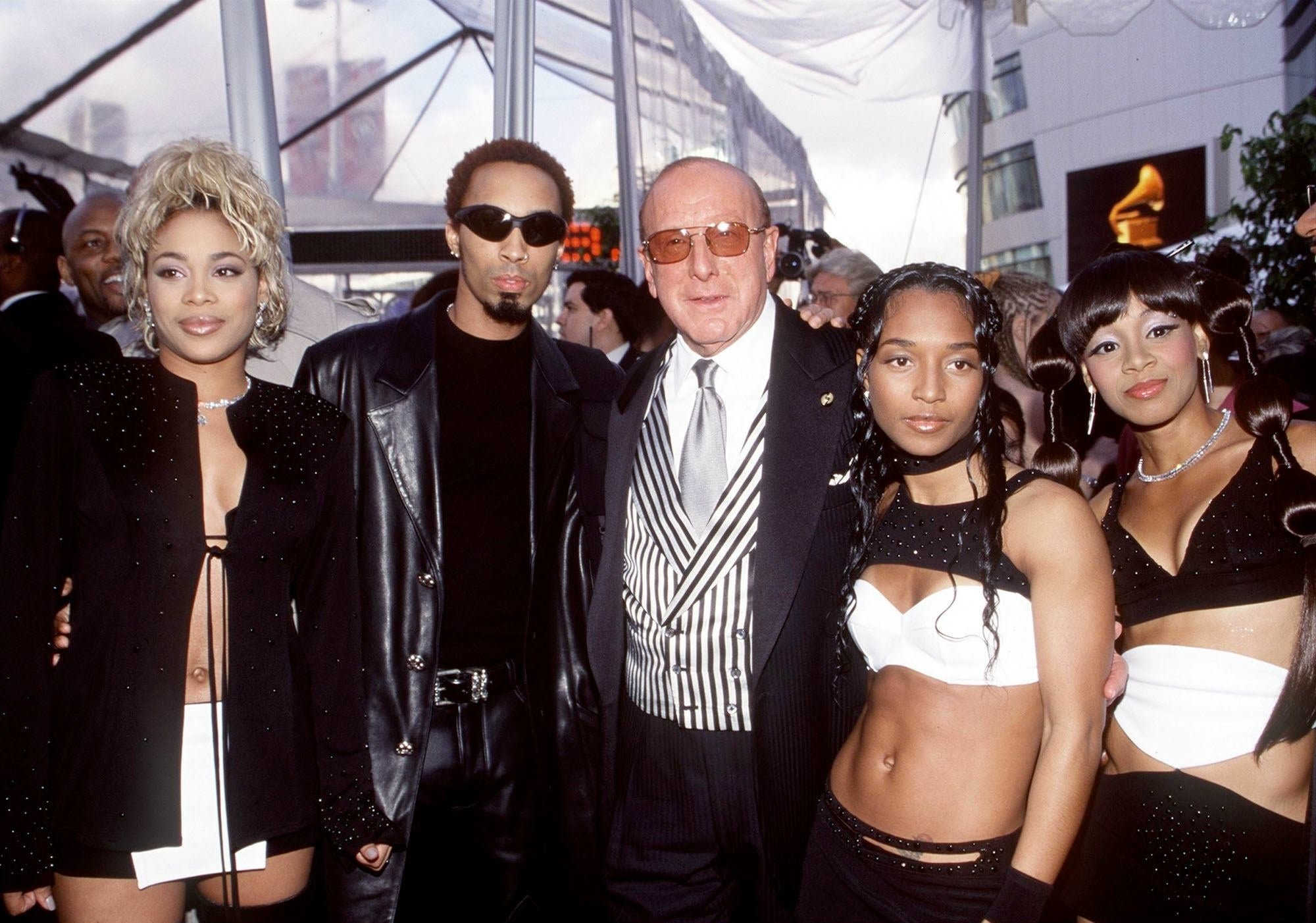 TLC  wearing matching outfits and Clive Davis on a red carpet
