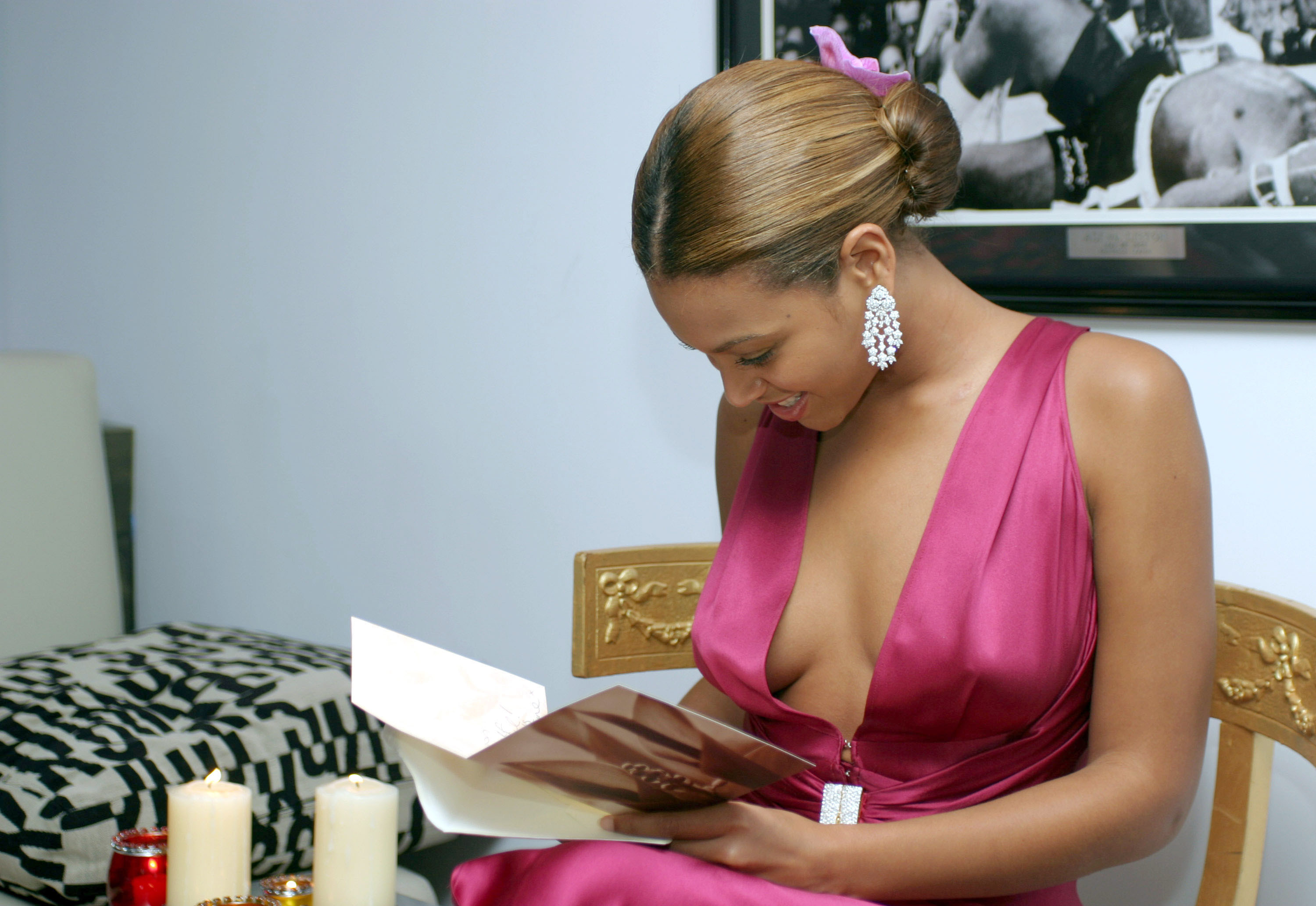 Beyonce reads a birthday card in a pink dress