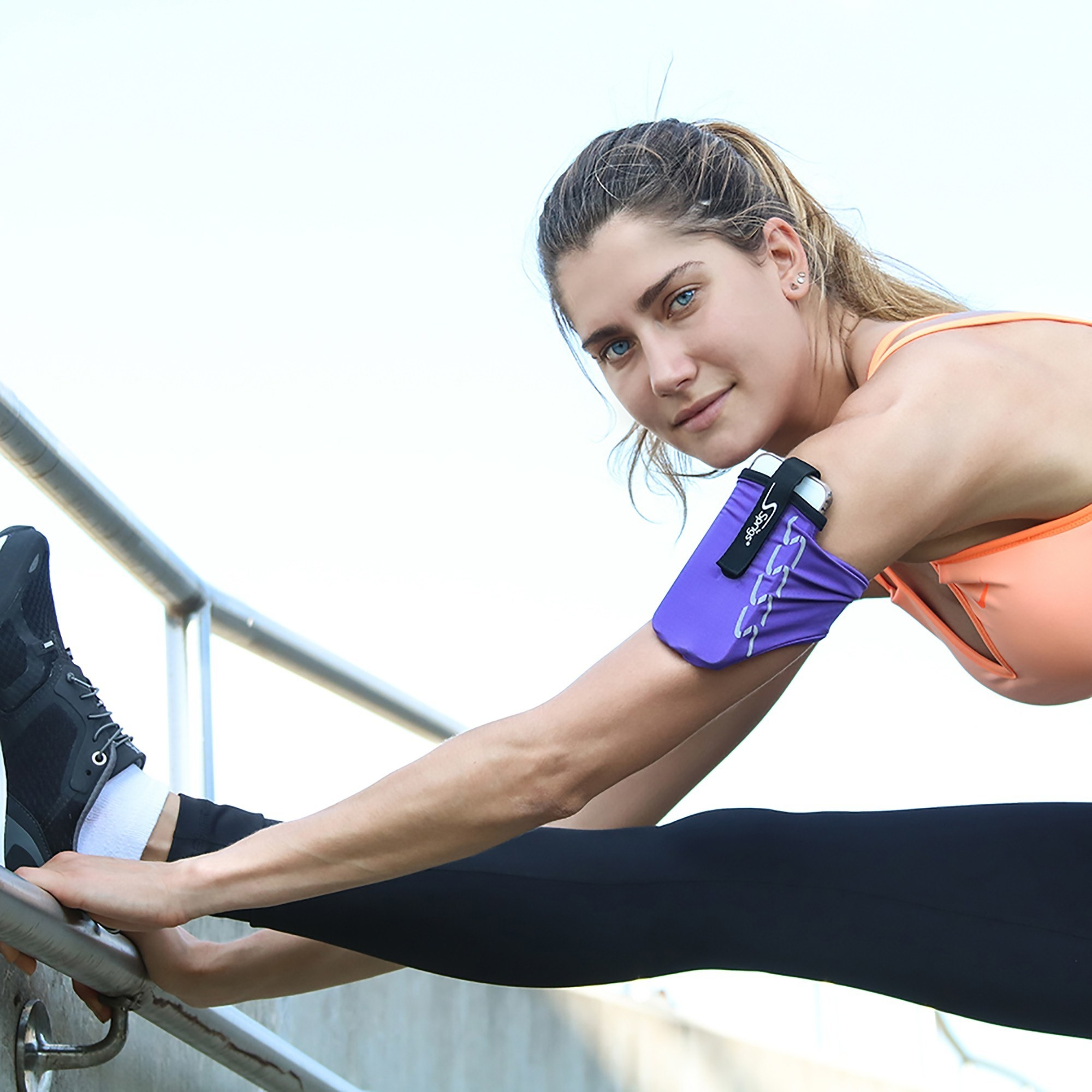 model stretches leg while wearing purple armband on their arm