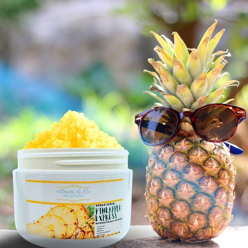 An open container of yellow body scrub next to a pineapple in sunglasses