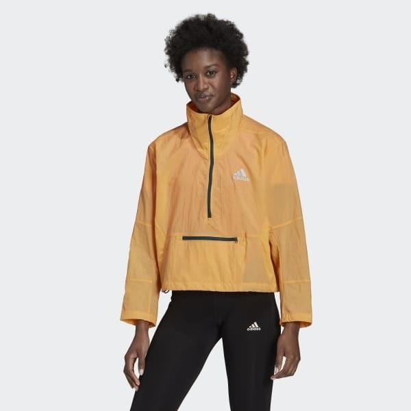 model wears light orange zip-up running jacket with black leggings