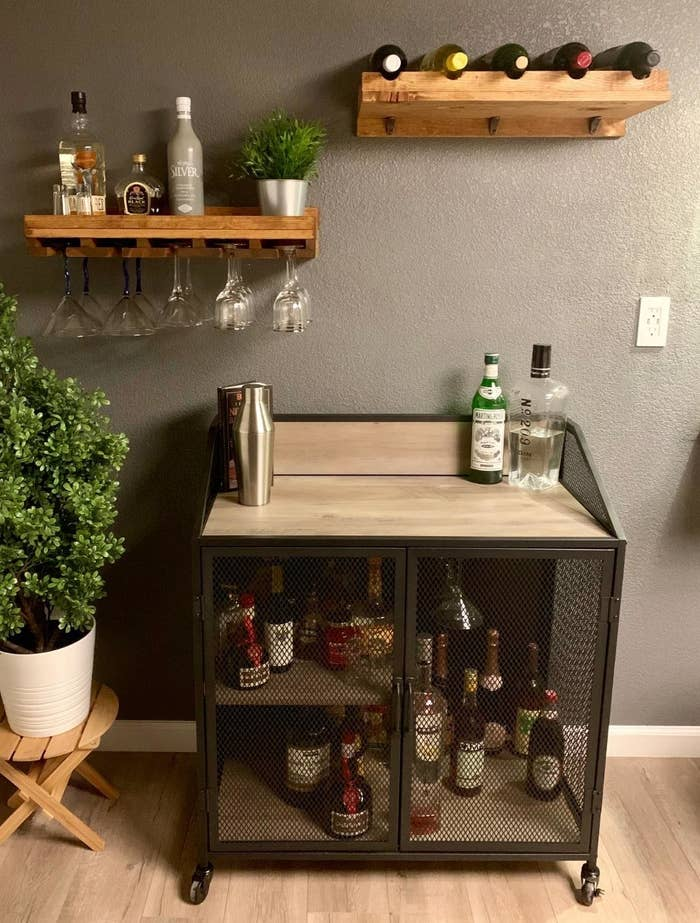 reviewer image of the Walker Edison Malcomb Urban Industrial Metal Mesh Double Door Rolling Bar Cabinet with several bottles of alochol in the cabinet space and a bottle of gin on its top surface