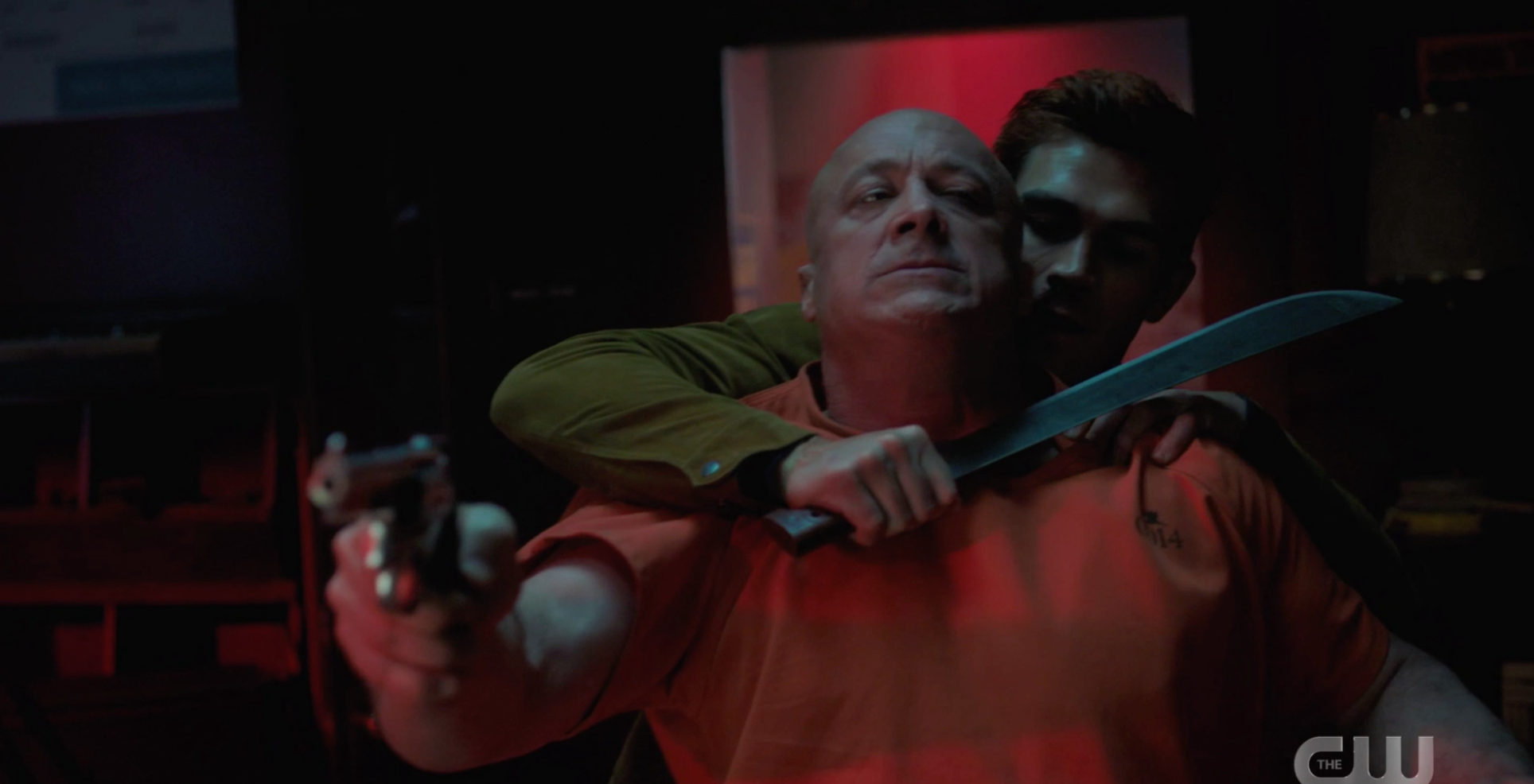 Archie holding a guy at sword point while he aims a gun