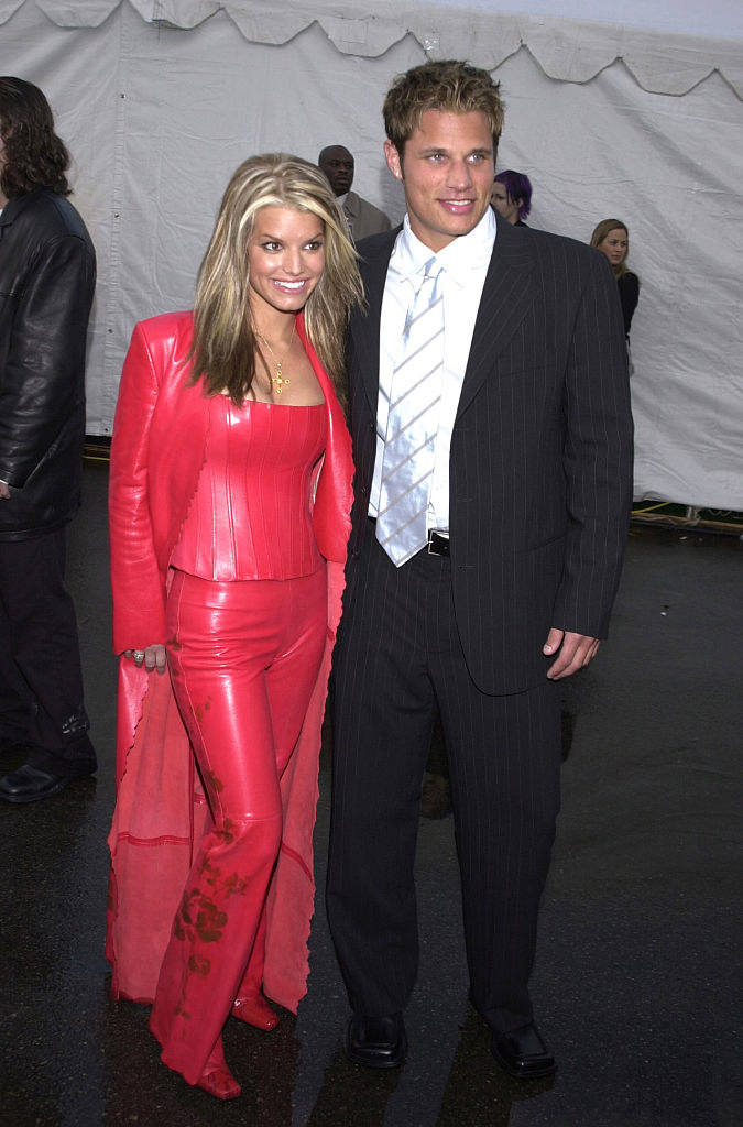 Jessica in a all red leather pant suite cape outfit standing next to Nick Lachey