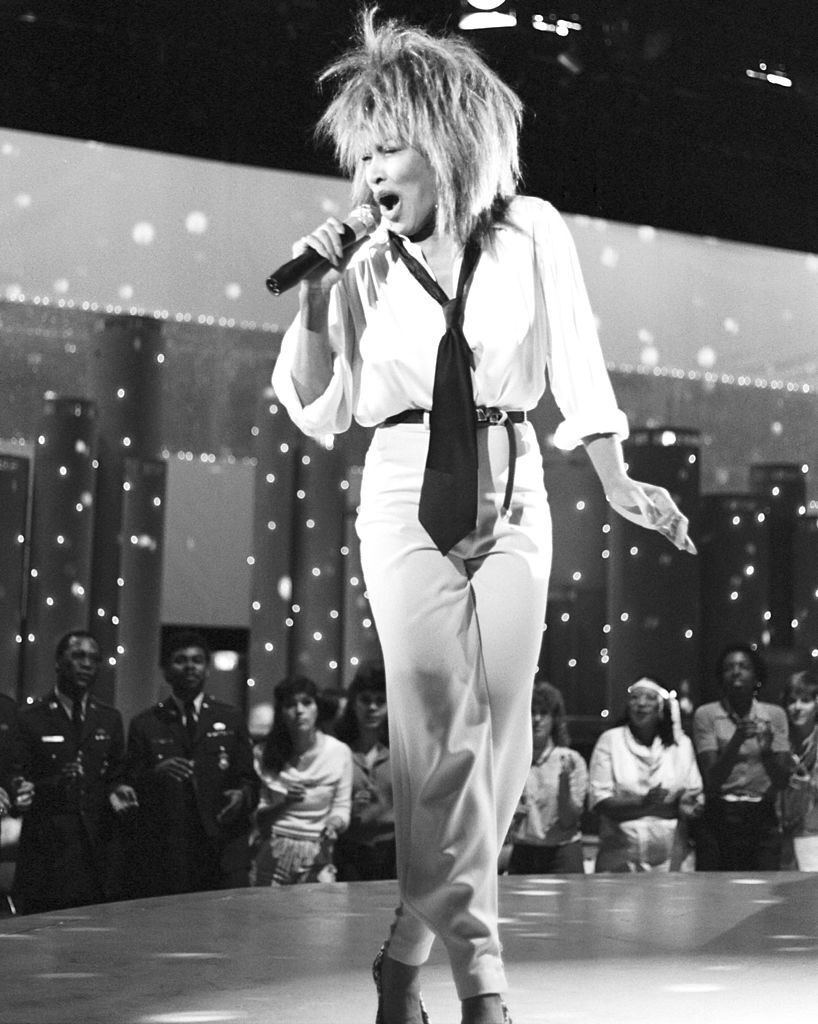 Tina Turner wears an open blouse with a loose tie