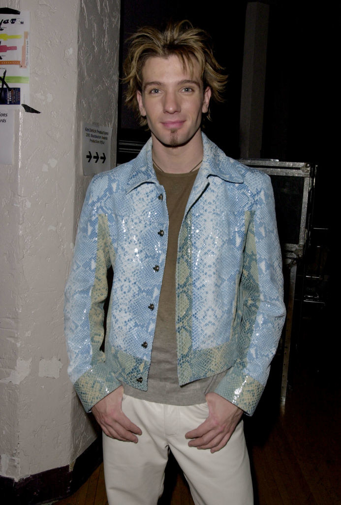 JC wearing a baby blue snakeskin jacket and sporting a cropped and layered, chunky highlighted haircut