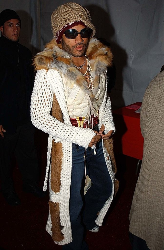 Lenny Kravitz backstage at the VMAs in a white knit floor length cardigan and leather top with fur collar
