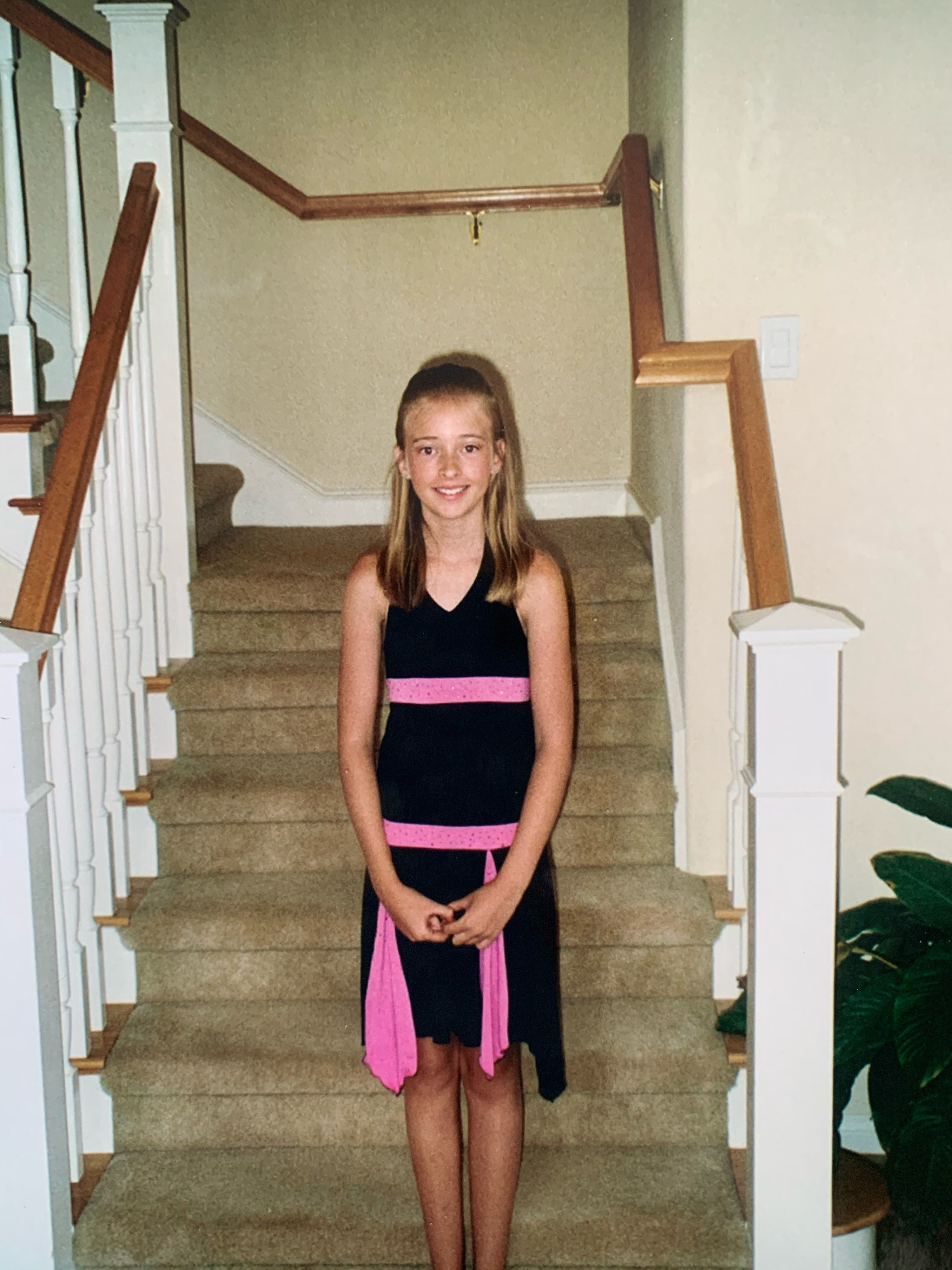 A girl wearing a simple black dress with bright pink embellishments