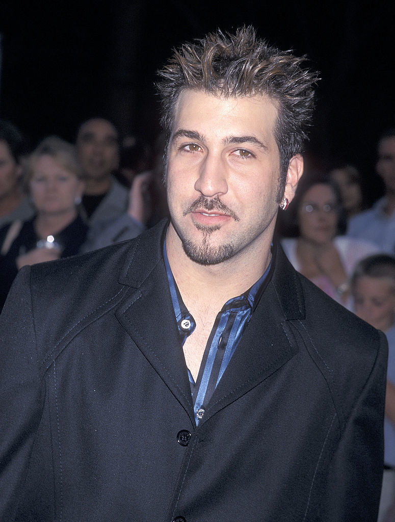 Joey on a red carpet in a black suit, stripped shirt, and with spikey gel'd hair