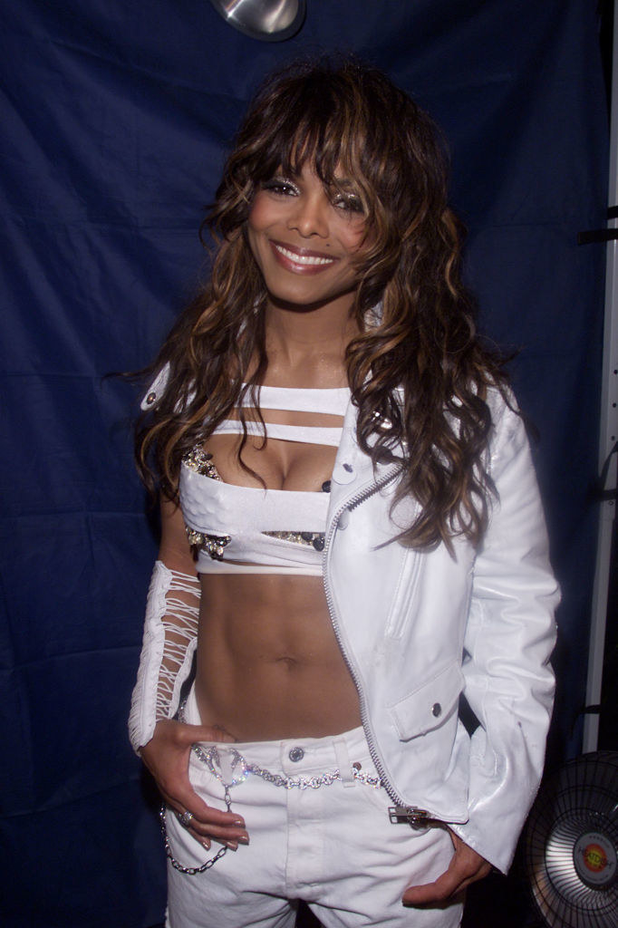 Janet Jackson backstage at an event in white jeans, white crop-top, and white leather jacket