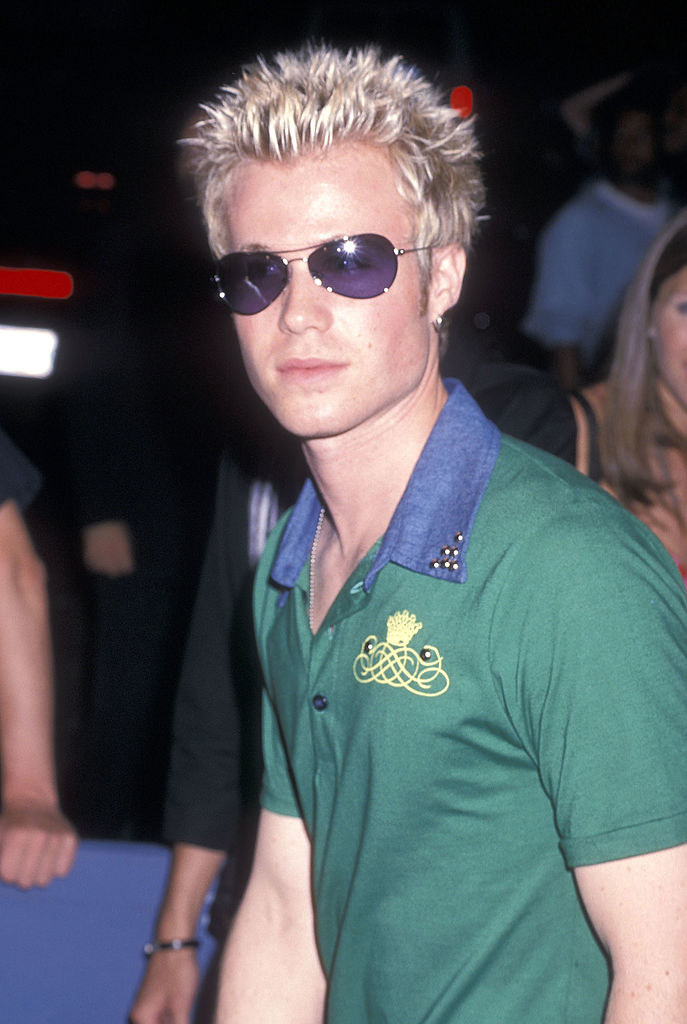 Ashley on the red carpet in a green polo, purple sunglasses and bleached blonde hair