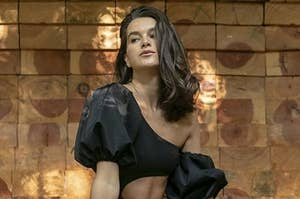 model wearing the one shoulder puff-sleeve one-piece with a cut-out in the stomache in black