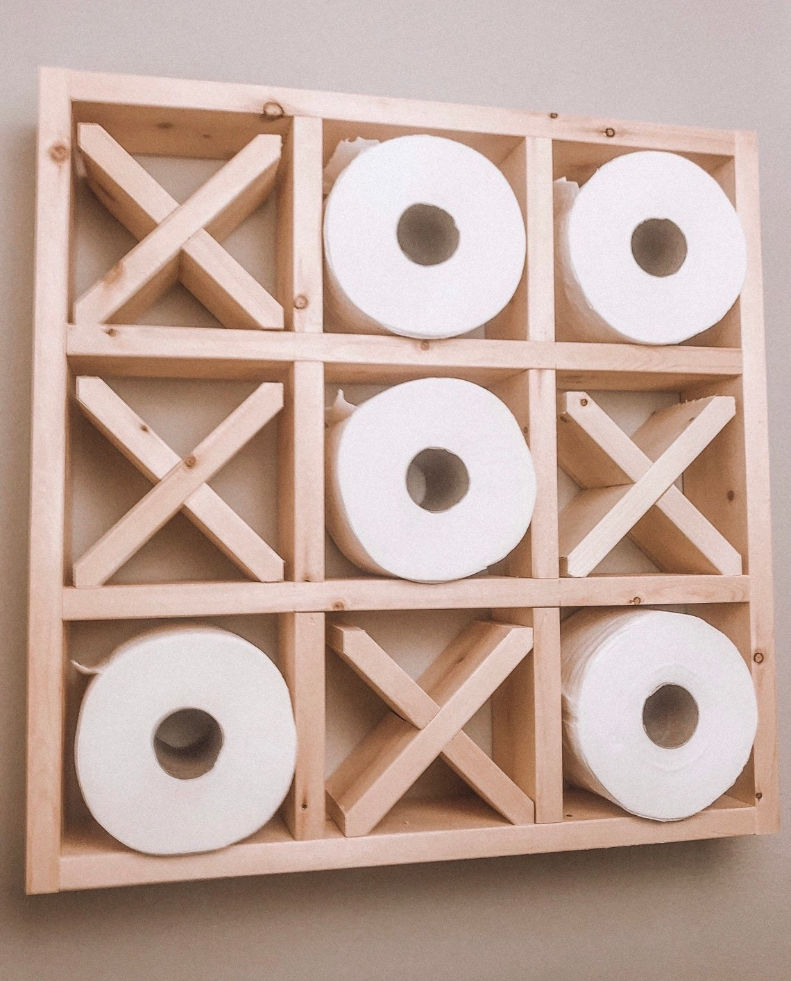 Wood shelf with nine squares. Four are filled with wooden X shapes and the rest are filled with toilet paper rolls.