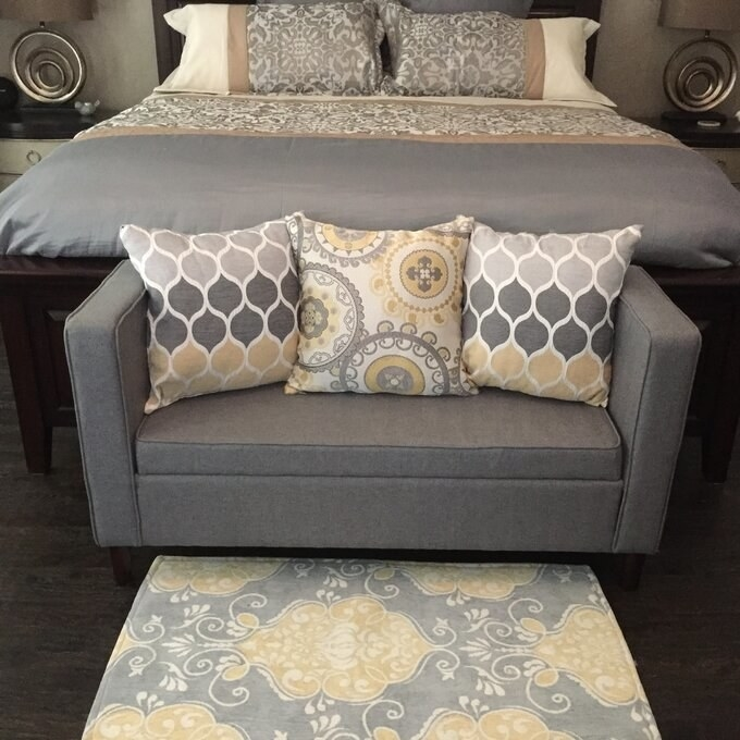 gray bench at the end of a reviewer's bed
