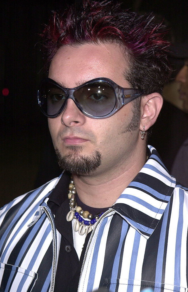 Christ wearing a stripped jacket, puka shell necklace, and purple sunglasses, while sporting purple spiked hair