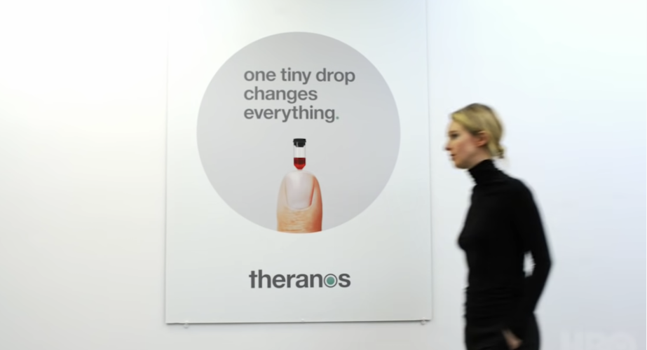 Elizabeth Holmes walks by an ad for her since-shuttered company, Theranos