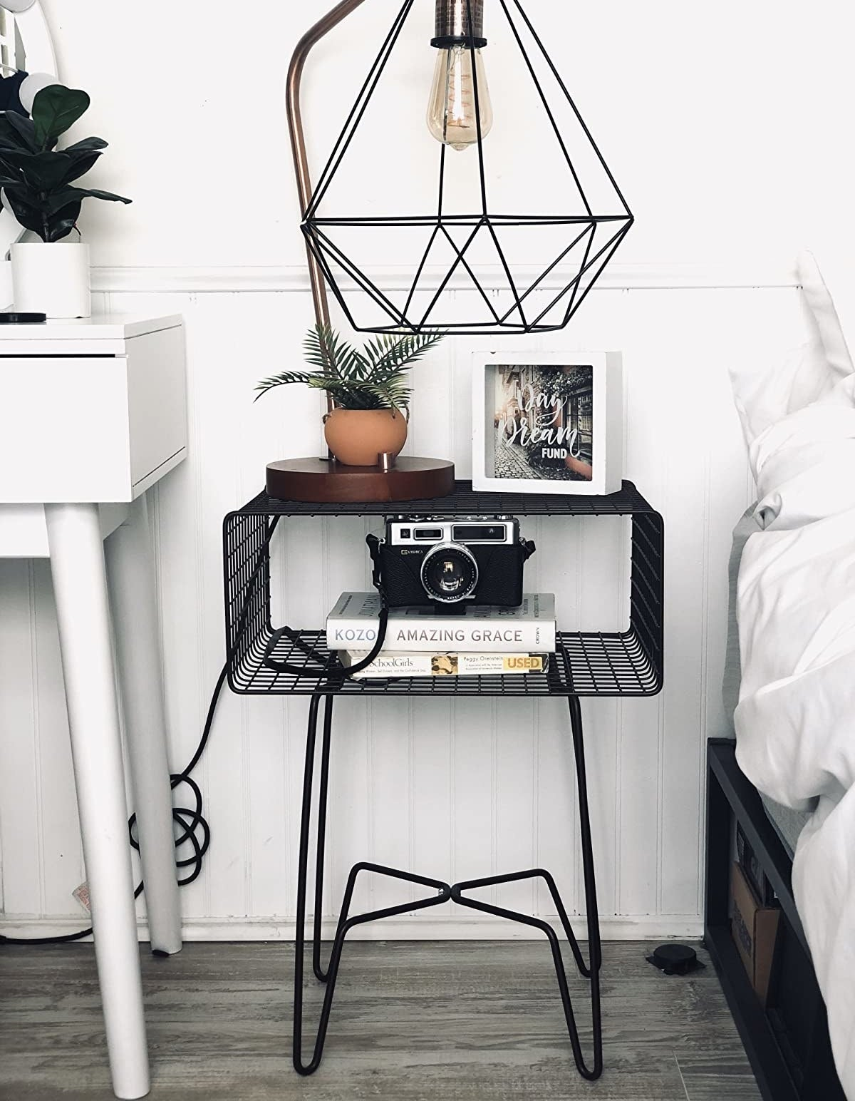 reviewer image of the black mDesign Modern desk in a white minimalist bedroom with a black geometric lamp on its surface