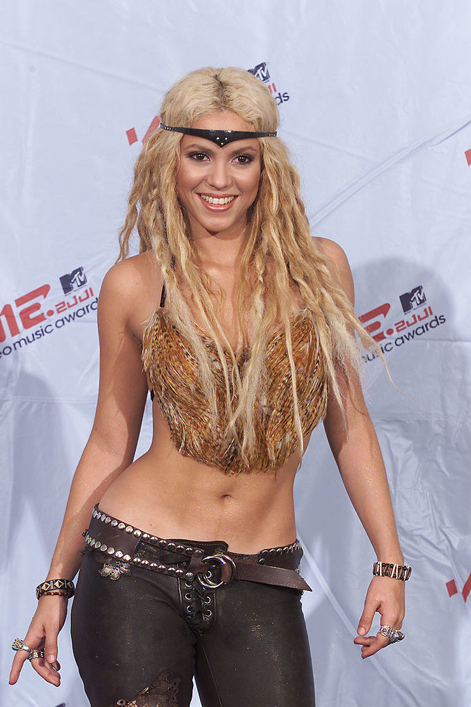 Shakira with blonde hair wearing a feather top leather pants