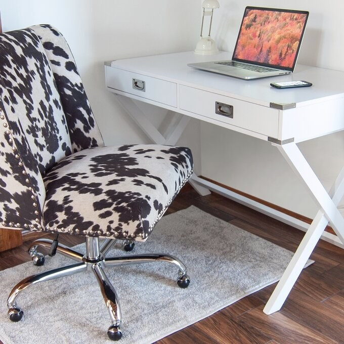 a reviewer's white desk with a laptop on top